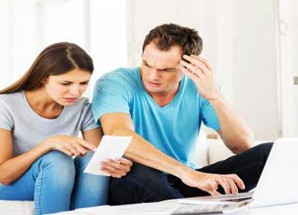 Couple With Laptop Examining Bills